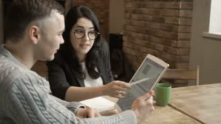Young man talks with woman looking at digital tablet
