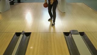 Young man throws bowling ball