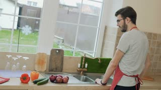 Young man washes pepper before add it in a salad