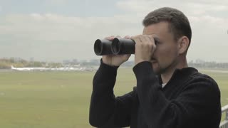 Young man with binoculars watches after planes in airport