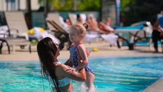 Young mother and her daughter having fun together in the swimming pool