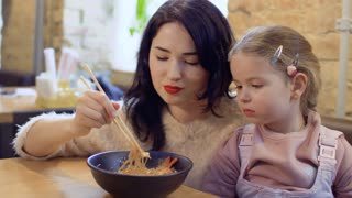 Young mother feed her little daughter with a korean noodles in restaurant