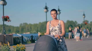 Young mother is walking with baby carriage at the embankment of the city