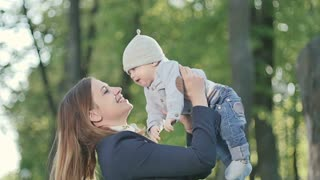 Young mother rejoice with little son in park