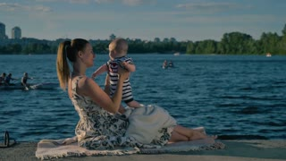 Young mother with baby are resting on background of passing canoe on the river