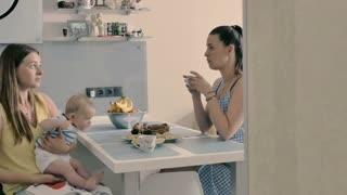 Young mother with baby drinks a tea with her friend at the kitchen at home