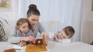 Young mother with children makes a gingerbread house at the kitchen