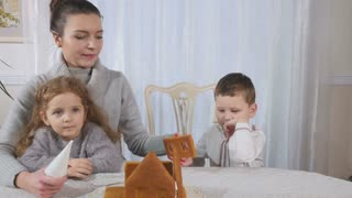 Young mother with two children makes a gingerbread house