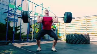 Young muscular guy training with barbell on the sports ground