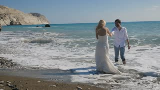 Young newlyweds rejoice in the ocean