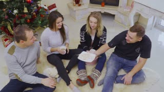 Young people eats marshmallow near Christmas tree