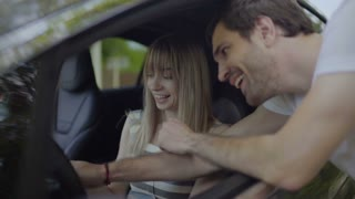 Young people laughing when guy show girl how to use a new car