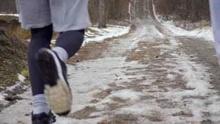 Young people runs along slippery road in slowmotion