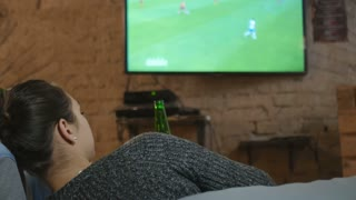 Young people watching football on TV and drinking beer