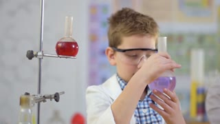 Young scientist holds flask with purple liquid and researches it