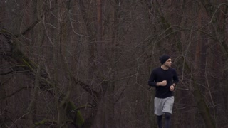 Young sportsman run out of dark wood
