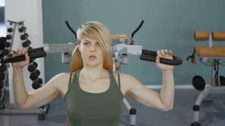 Young sporty woman on training apparatus in the gym