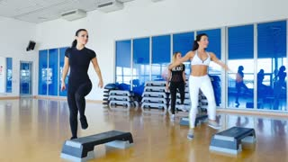 Young sporty women training the step aerobics in the gym