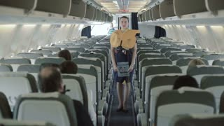 Young stewardess presents the safety instruction