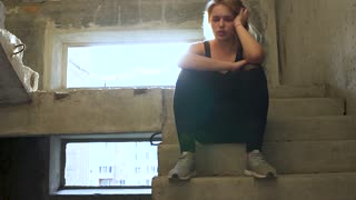 Young unhappy girl is sitting at the stairs in an abandoned building