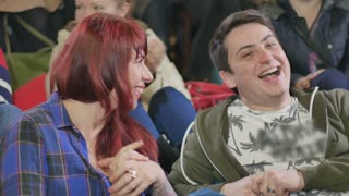 Young woman and handsome man laughing on the comedy show
