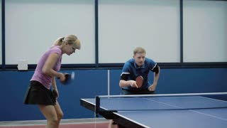 Young woman and man together playing in a table tennis