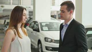 Young woman buy a car in the car dealership