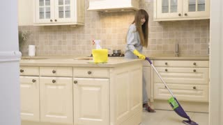 Young woman clean floor with mop and dancing