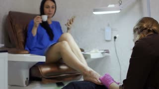Young woman enjoys the procedure of making pedicure in salon