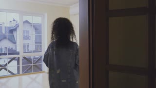 Young woman examines an empty room in a new house