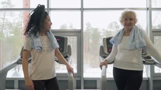 Young woman high-five with elderly woman standing near treadmill