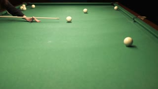 Young woman hit the billiard ball into a pocket
