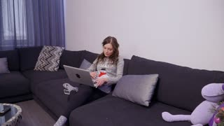 Young woman in grey sweater use laptop at home