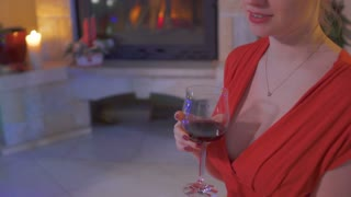 Young woman in red dress with big decollete drink red wine