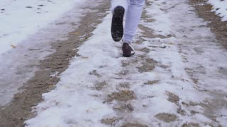 Young woman in snickers runs on snow road in slowmotion