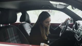Young woman inspects the car's cabin in the car dealership