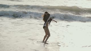 Young woman jumps and rejoices on the beach of sea