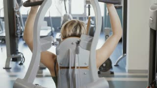 Young woman makes exercise for back on training apparatus