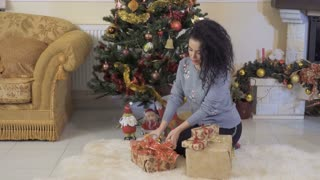 Young woman packs the Christmas gifts