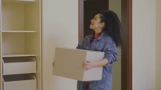 Young woman put the box with things in a wardrobe in a new home