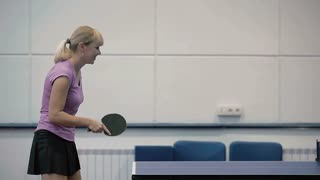 Young woman quickly hits the ball in the table tennis