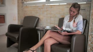 Young woman read a magazine and wait her turn in barbershop