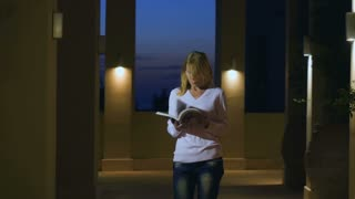 Young woman read the journal in huge hall with muffled light