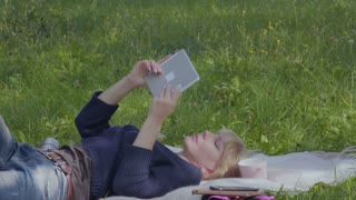 Young woman relax on blanket in park and uses digital tablet