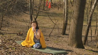 Young woman relaxing with tea after training in park