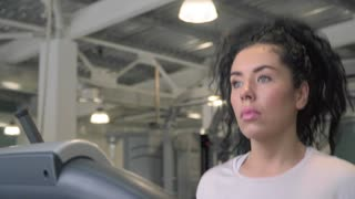 Young woman run on treadmill in gym