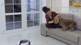 Young woman strokes her dog because he afraid of vacuum-cleaning robot