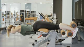 Young woman training back on the training apparatus in gym