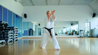 Young woman training the karate tricks in the gym