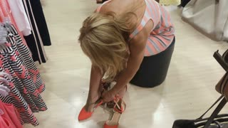 Young woman try on shoes in the shop